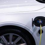 Weißes Elektroauto wird mit einem gelben Stromkabel geladen
