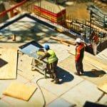 Zwei Bauarbeiter auf einer Baustelle mit einer Säge und herumliegenden Holzbrettern
