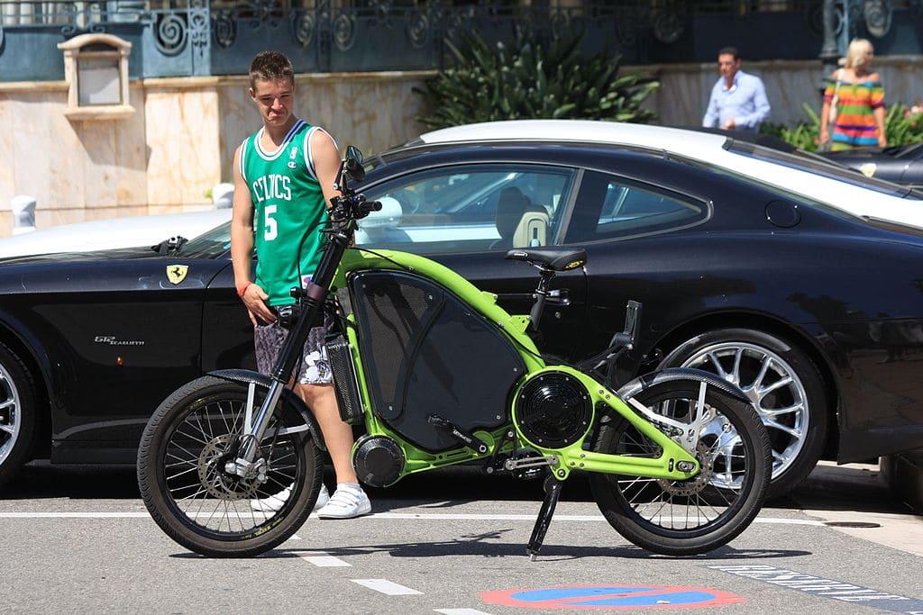 Ein eRockit parkt neben einem Ferrari und wird von einem Jugendlichen staunend angeschaut.