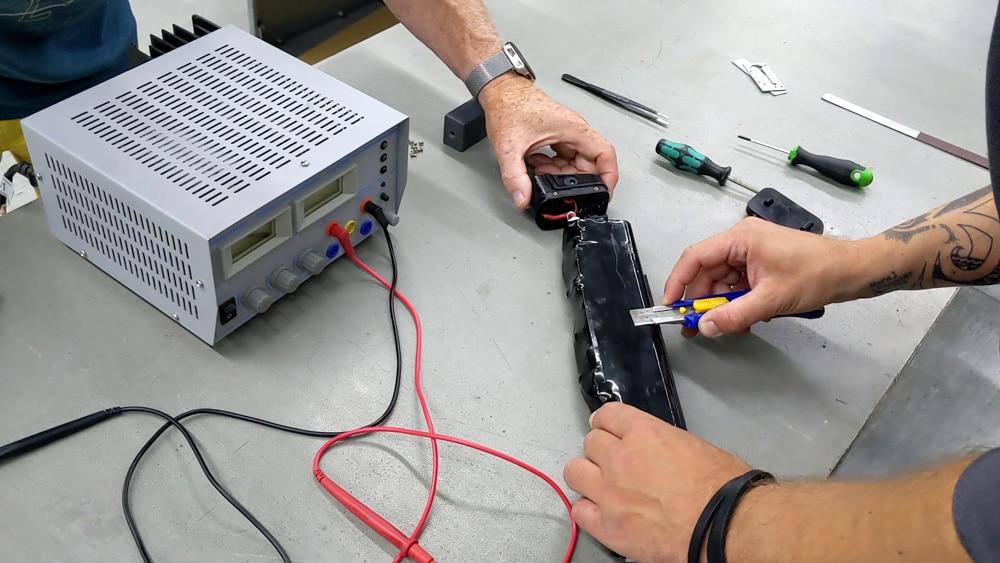 Schrumpfschlauch des Corepacks einer E-Bike-Batterie wird mit einem Cutter-Messer aufgeschnitten.
