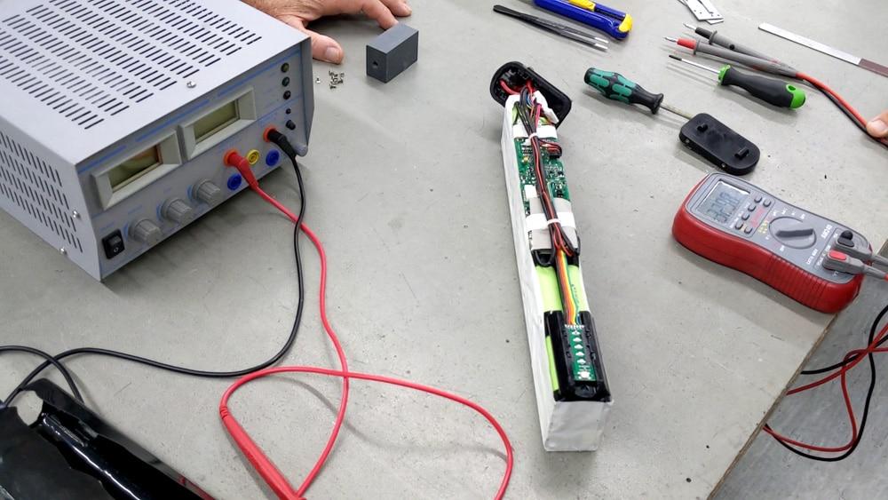 Ein offener Akkupack mit sichtbaren Zellen und BMS liegt auf einem Tisch neben einem Ladegerät und Werkzeugen.