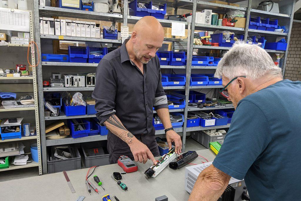 Jan Hetzel zeigt mit dem Finger auf ein Kabel auf einem geöffneten E-Bike-Akku.