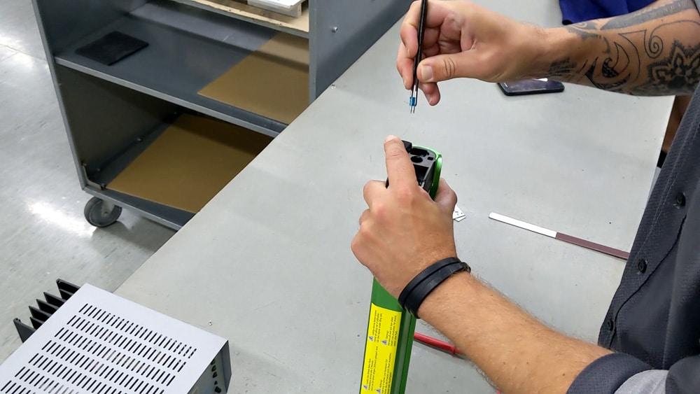 Eine Sicherung wird mit einer Pinzette von der Oberseite eines Pedelec-Akkus herausgezogen.