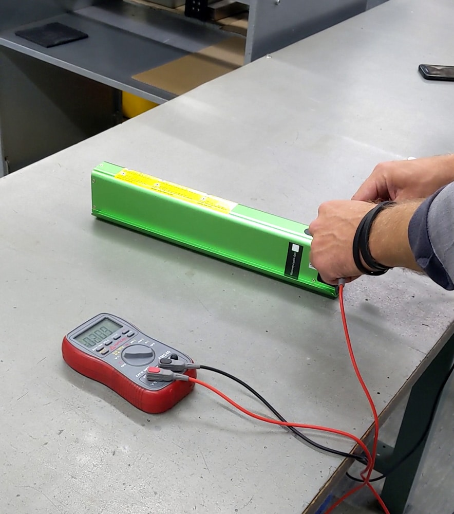 Mit einem Multimeter wird bei einem E-Bike-Akku mit grünem Gehäuse die Spannung gemessen.