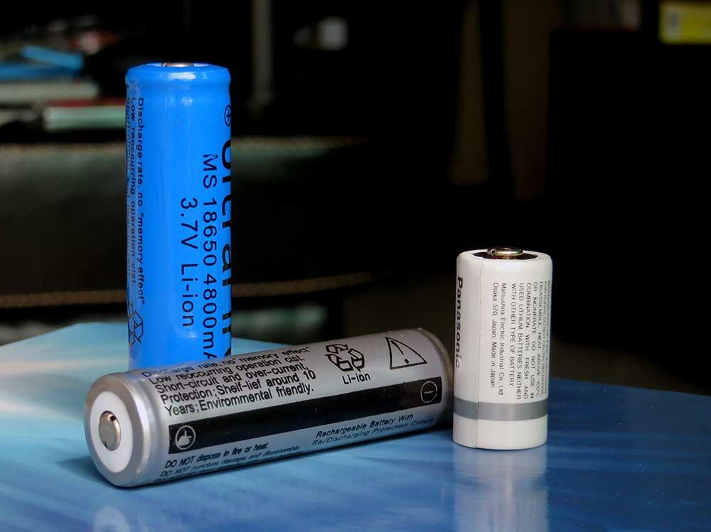 Zwei große und eine kleine zylindrische Lithium-Ionen-Zellen auf einem Tisch