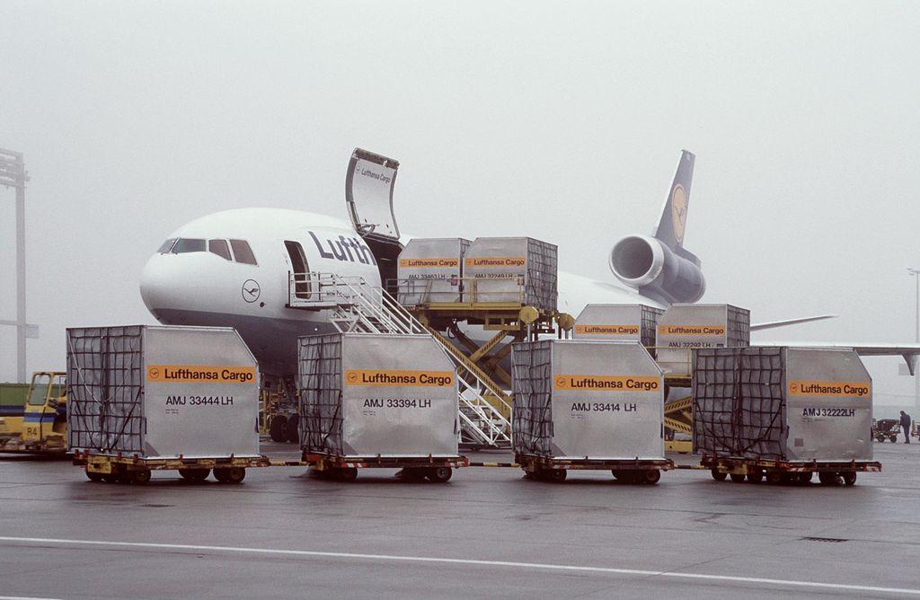 Frachtflugzeug mit offener Ladeluke an der Seite. Container stehen vor dem Flugzeug und werden hineingeladen.