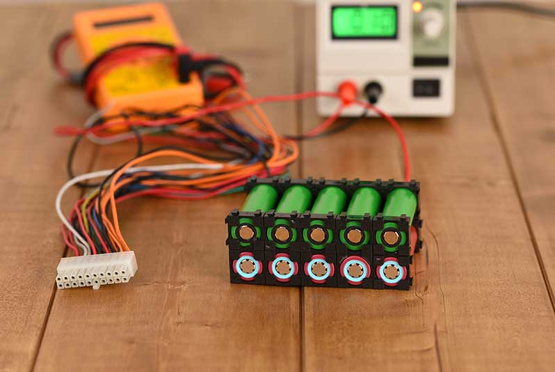 Ein Akkupack mit 10 Zellen in zwei Reihen liegt an ein Ladegerät angeschlossen auf einem Holztisch
